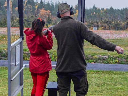 En kvinne øver på å skyte sammen med en instruktør.