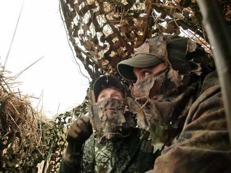 To jegere som gjemmer seg for fuglevilt.